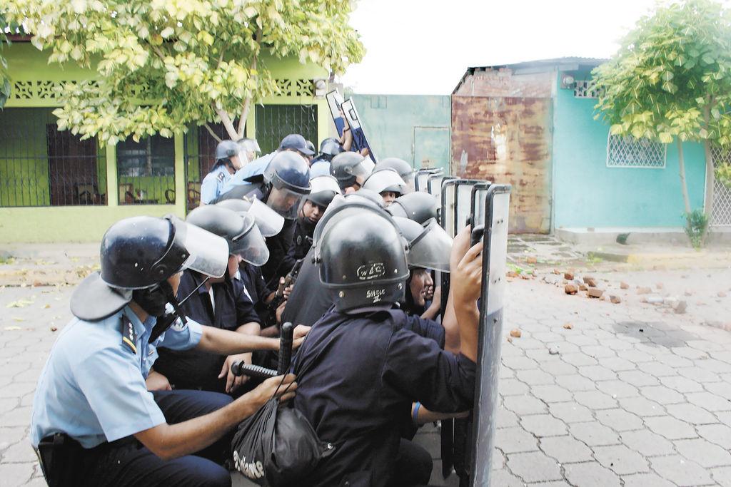 Miembros de las Fuerzas Especiales de la Policía Nacional se resguardan tras los escudos ante el ataque de las turbas. LA PRENSA/ E. LÓPEZ