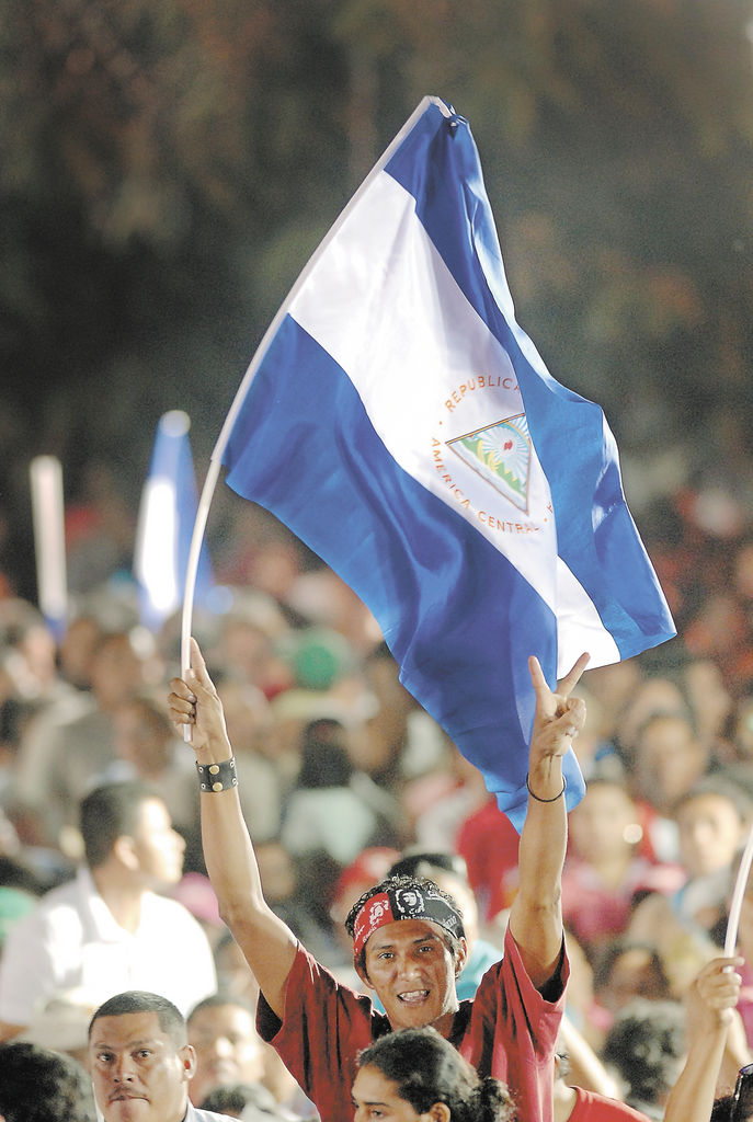 Un simpatizante del partido de gobierno alza la Bandera de Nicaragua en el acto de juramentación de los CPC  en noviembre del   2007.