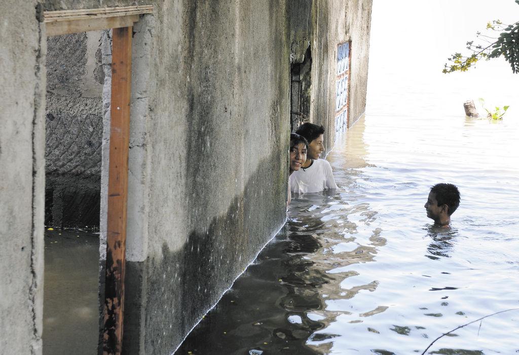 Nelson Díaz Mercado se asoma por la ventana de su casa, pero no lo hace desde adentro. Él está afuera, viendo hacia el interior de lo que fue la vivienda. El piso está cubierto por las aguas del lago Xolotlán. LA PRENSA/B. PICADO