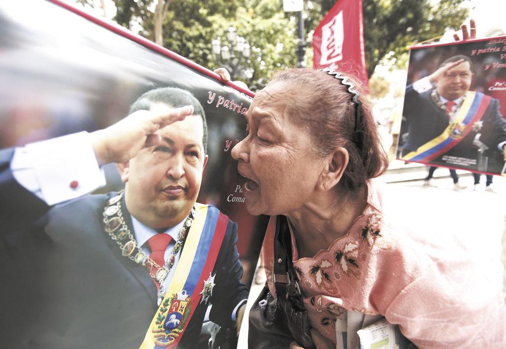 """Una simpatizante del presidente Hugo Chávez grita """"te amo"""" al mandatario expuesto en un póster, durante un encuentro de chavistas que se reunieron en la Plaza Bolívar, en Caracas, para manifestarle apoyo a su líder.  LA PRENSA/AP/FERNANDO LLANO"""