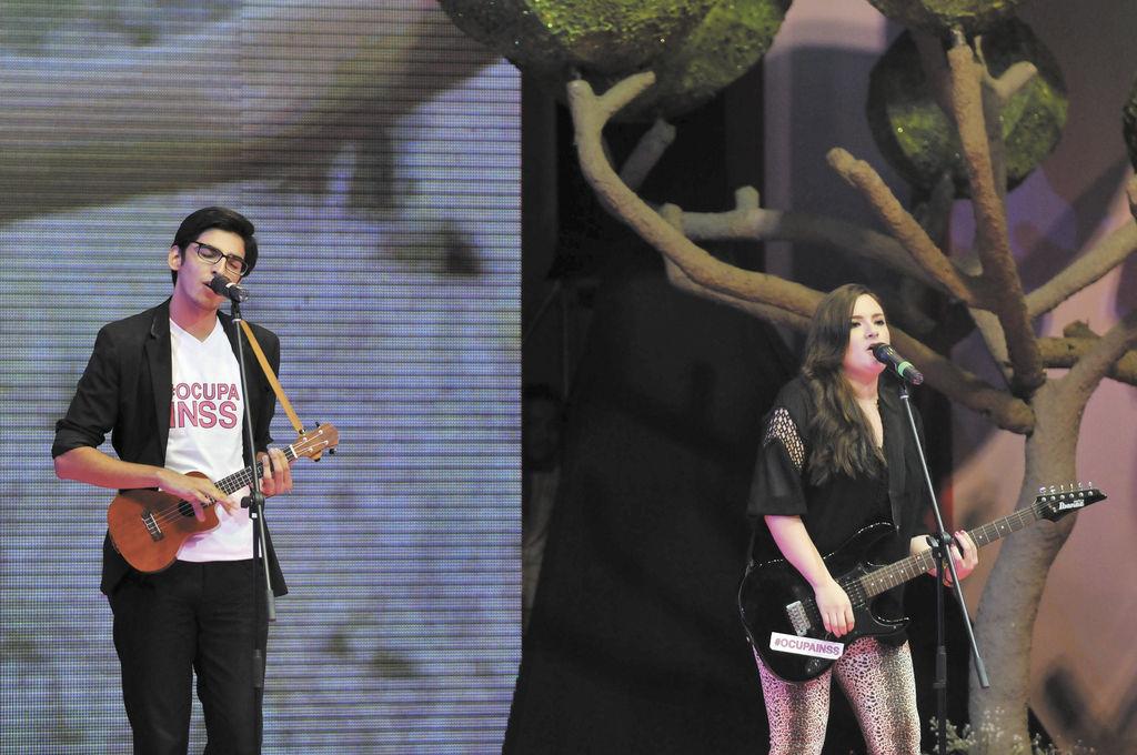 """Usando la camiseta de OCUPA INSS, Sebastián y Nina se solidarizaron con la lucha de los """"viejitos"""" el pasado sábado 22 de junio durante la elección de Miss Teen 2013.  LA PRENSA/ARCHIVO"""