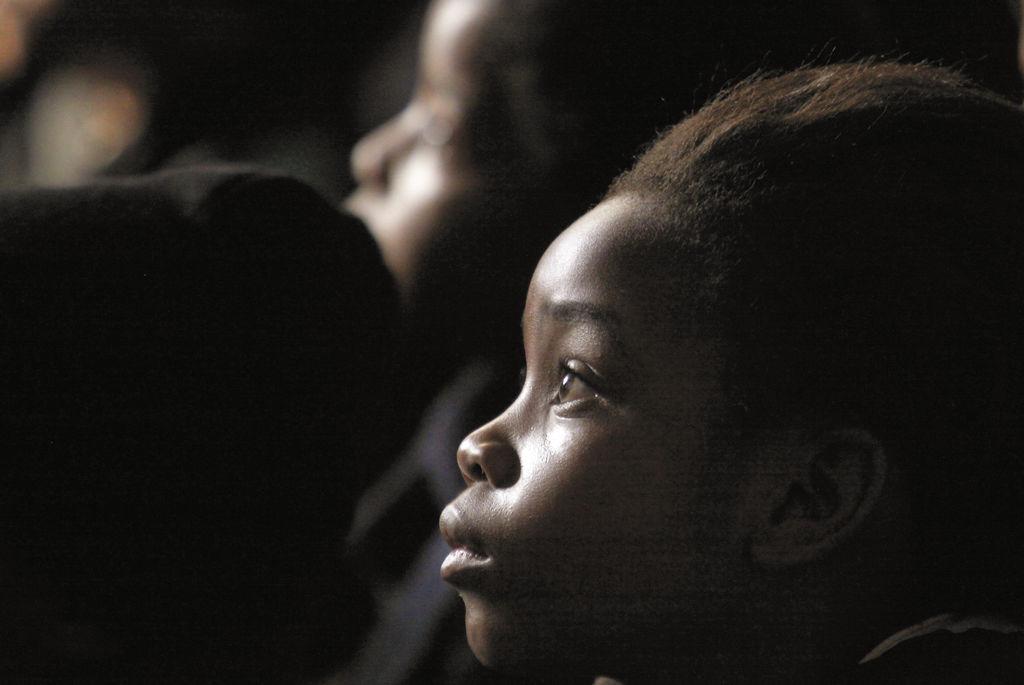 En la escuela, niños sudafricanos escuchan la historia de Nelson Mandela.