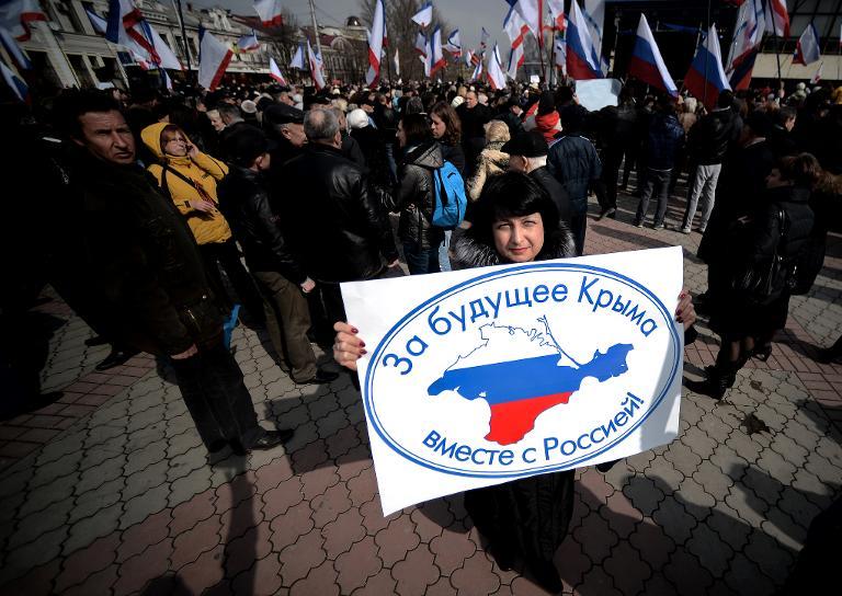 Una mujer muestra un cartel con el mapa de la región ucraniana de Crimea coloreado con la bandera rusa, en Simferopol, el 9 de marzo de 2014