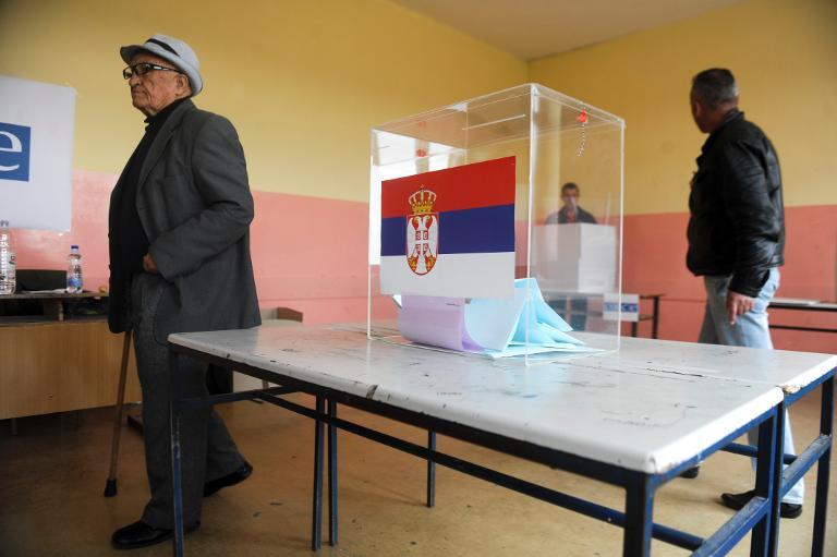 Serbios kosovares abandonan un local de votación tras sufragar, en Gracanica, distrito gobernado por Serbia, el 16 de marzo de 2014, durante la celebración de las legislativas anticipadas.