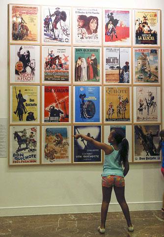 Una niña ante carteles de películas de El Quijote durante la jornada de puertas abiertas en la sede central del Instituto Cervantes, en Madrid. LA PRENSA/EFE/Paco Campos
