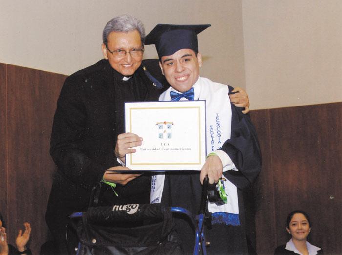 Antonio sostiene su título de licenciado en Diseño Gráfico, junto al rector de la UCA, José Alberto Idiáquez, el pasado mes de mayo en su graduación.