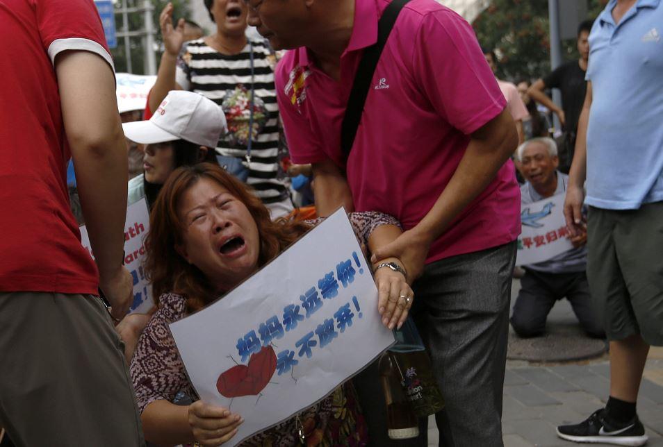 Familiares chinos del vuelo MH370 de Malaysia Airlines lloran delante de los medios de comunicación ante la Embajada de Malasia en Pekín  LAPRENSA/EFE