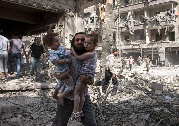 SIRIA: Un hombre carga a sus dos hijas en Aleppo, la ciudad más poblada de Siria. LA PRENSA/AFP Photo/Karam