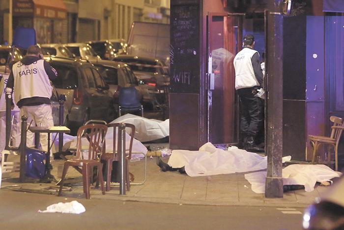 Varias víctimas de los ataques yacen  frente a la entrada de uno de los  restaurantes atacados anoche en el centro de París.  LA PRENSA/AP