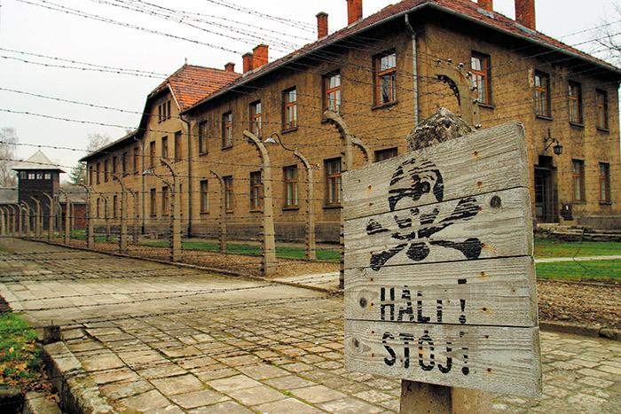 """Señal de """"¡alto!"""" en alemán  y polaco, contiguo al sistema de alambrado que dividía a presos y autoridades."""