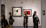 Varias personas observan algunas obras del artista callejero británico Banksy durante la presentación de la exposición