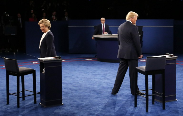 Democratic nominee Hillary Clinton (L) and Republican nominee Donald Trump arrive on stage during the second presidential debate at Washington University in St. Louis, Missouri on October 9, 2016. / AFP PHOTO / POOL / JIM BOURG