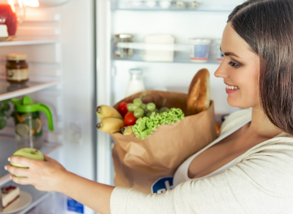 Beautiful pregnant woman is holding a paper bag with food and smiling while putting food into fridge at home