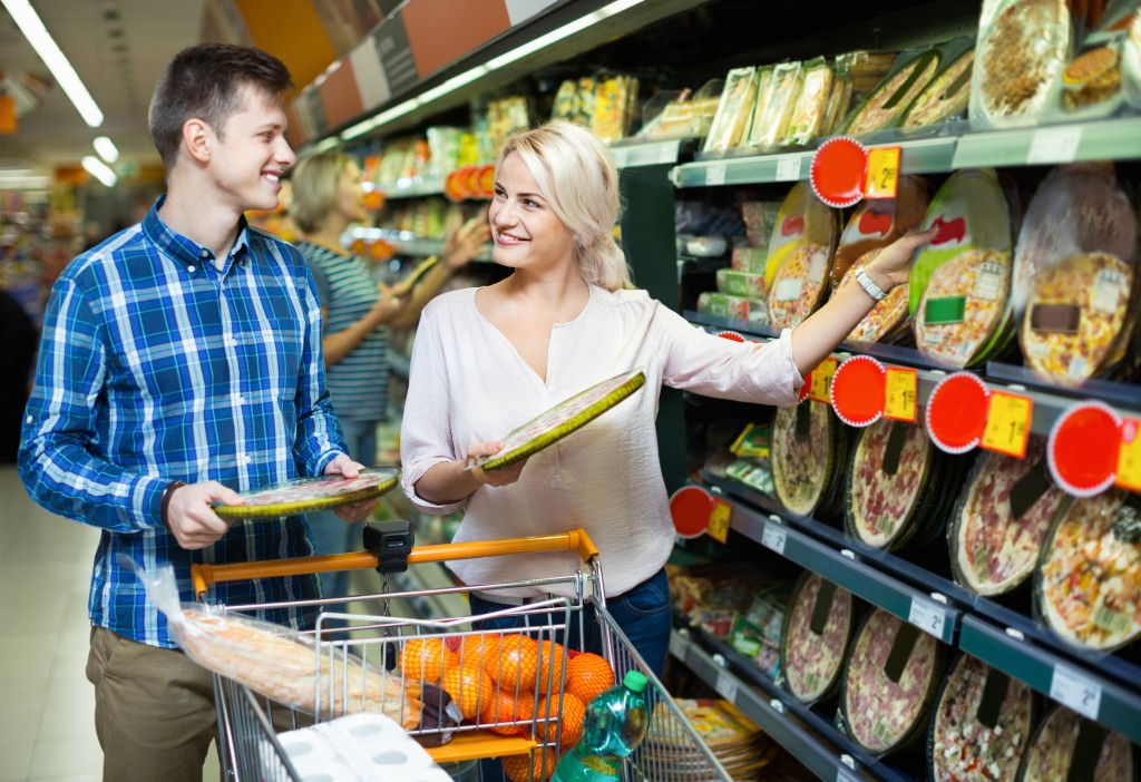 Satisfied family couple choosing chilled pizza in food shop