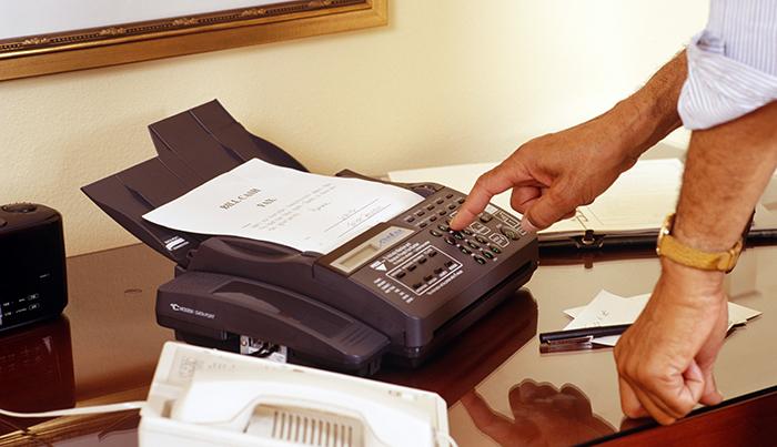 Man using fax machine, Close-up of hands