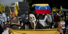 Un manifestante que lleva una máscara de fantasma y sostiene una pancarta que dice basta, en la marcha en contra el presidente venezolano Nicolás Maduro. LA PRENSA/AFP