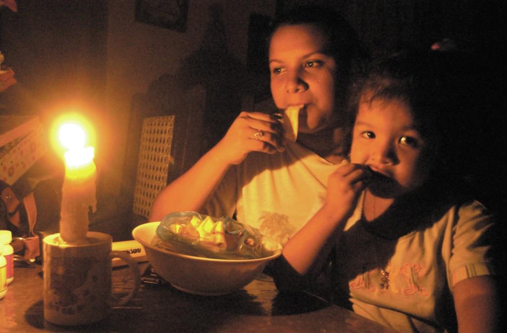 Yesenia Rivera Chavarría, junto a su hija de 3 años Judith Suazo Rivera, cenan en su casa de habitación en el barrio Batahola Norte, bajo la luz de una vela, producto de los apagones que se realizaron la noche del 2 de junio, 2006. GERMAN MIRANDA/LA PRENSA