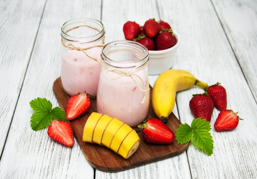 yogurt with fresh strawberries and banana on a old wooden table
