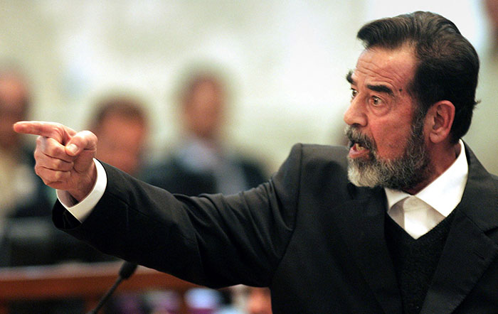 """FILE - In this Jan. 29, 2006 file photo, former Iraqi president Saddam Hussein gestures during his trial in Baghdad, Iraq. In the beginning, it all looked simple: topple Hussein, destroy his purported weapons of mass destruction and lay the foundation for a pro-Western government in the heart of the Arab world. ¶ Nearly 4,500 American and more than 100,000 Iraqi lives later, the objective now is simply to get out _ and leave behind a country where democracy has at least a chance, where Iran does not dominate and where conditions may not be good but """"good enough."""" (AP Photo/Darko Bandic, File)"""