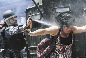 BRA021. RÕO DE JANEIRO (BRASIL), 16/11/2016.- Un policÌa brasileÒo rocÌa con gas a una manifestante durante una protesta contra el paquete de medidas del Gobierno contra los funcionarios p˙blicos del estado de RÌo de Janeiro hoy, miÈrcoles 16 de noviembre 2016, afuera de la Asamblea Legislativa, en la ciudad de RÌo de Janeiro (Brasil). EFE/Antonio Lacerda
