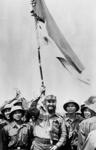 (FILES) This file photo taken on September 1973 shows Cuban First Secretary of the Cuban Communist party and President of the State Council Fidel Castro (C) holding a flag during his visit in South Vietnam during the Vietnam war. Cuban revolutionary icon Fidel Castro died late on November 25, 2016 in Havana, his brother, President Raul Castro, announced on national television. / AFP PHOTO / AVI / -