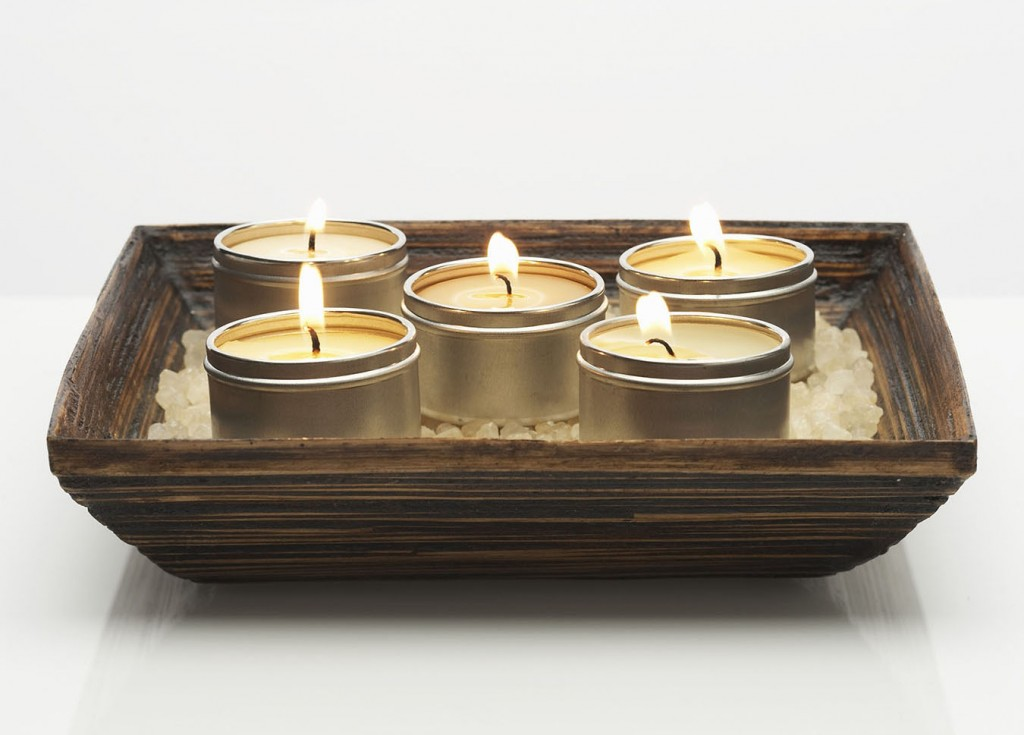 Five aromatherapy candles atop amber sea salt in wooden bowl