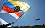 Un hombre sostiene una bandera nacional colombiana con rayas blancas durante una manifestación para exigir el respaldo inmediato del nuevo acuerdo de paz. AFP