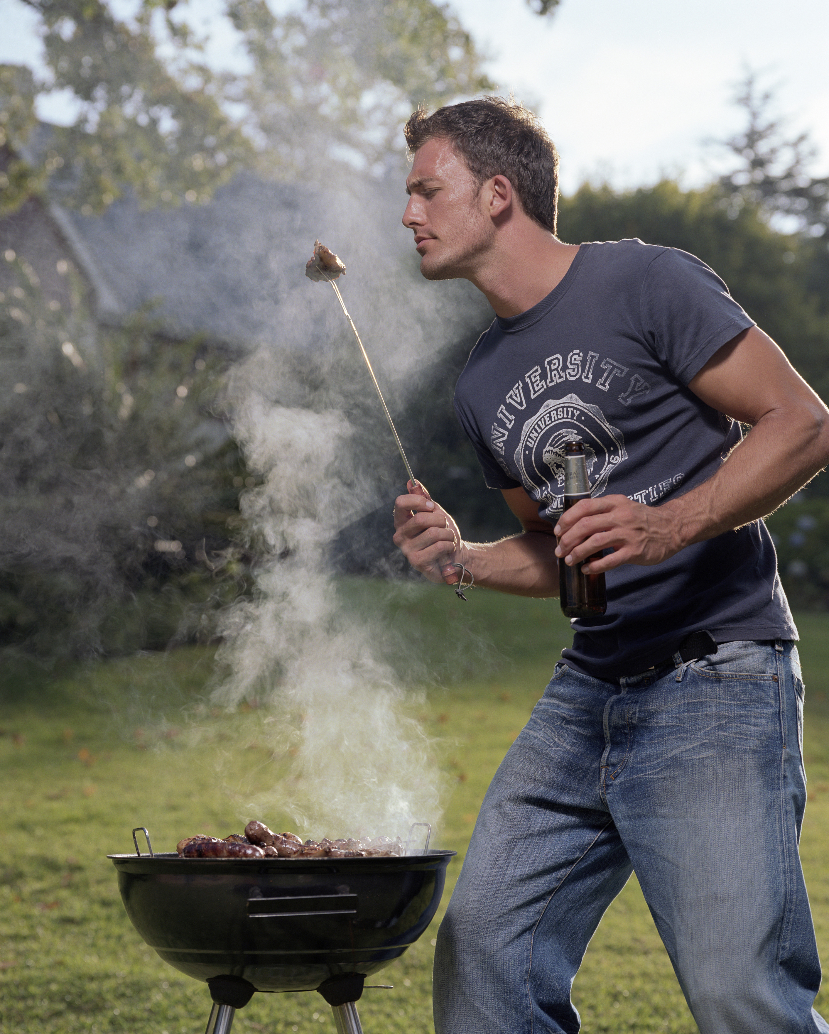 Young man tending barbecue, looking at skewered food