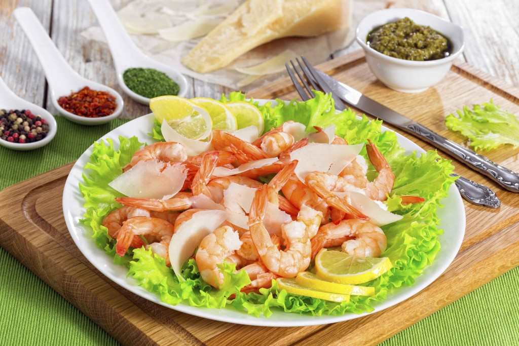 prawns, green lettuce leaves, slices of parmesan cheese salad on white plate with vintage fork and knife. Piece of parmesan, spices and sauce pesto on wooden background, view from above, close-up