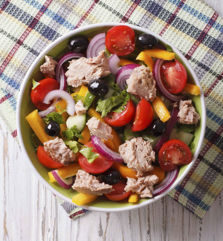 Fresh salad with tuna fish and vegetables in a bowl on the table. vertical top view